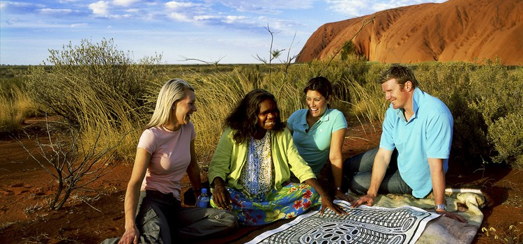 People looking at an Aboriginal painting with Uluru in the background